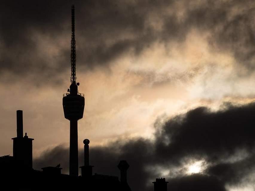 Kamine und der Stuttgarter Fernsehturm stehen bei Sonnenaufgang als Schattenriss vor Wolken. Foto: Sebastian Gollnow