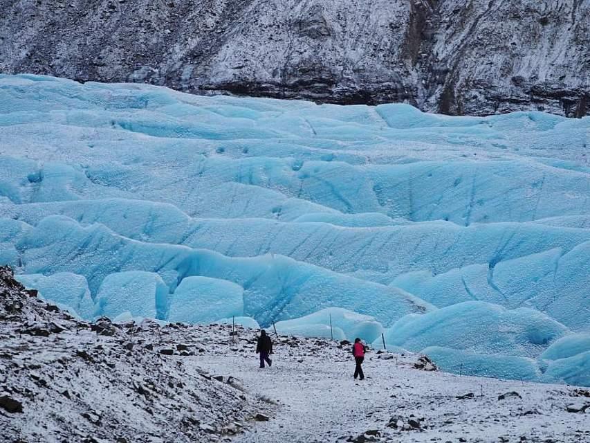Zwei Wanderer passieren den Gletscher Svinafellsjökull auf Island. Foto: Owen Humphreys/PA Wire