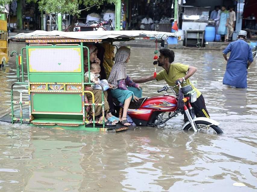 Menschen waten durch die durch starke Regenfälle überfluteten Straßen in der pakistanischen Stadt Lahore. Foto: K.M. Chaudary/AP