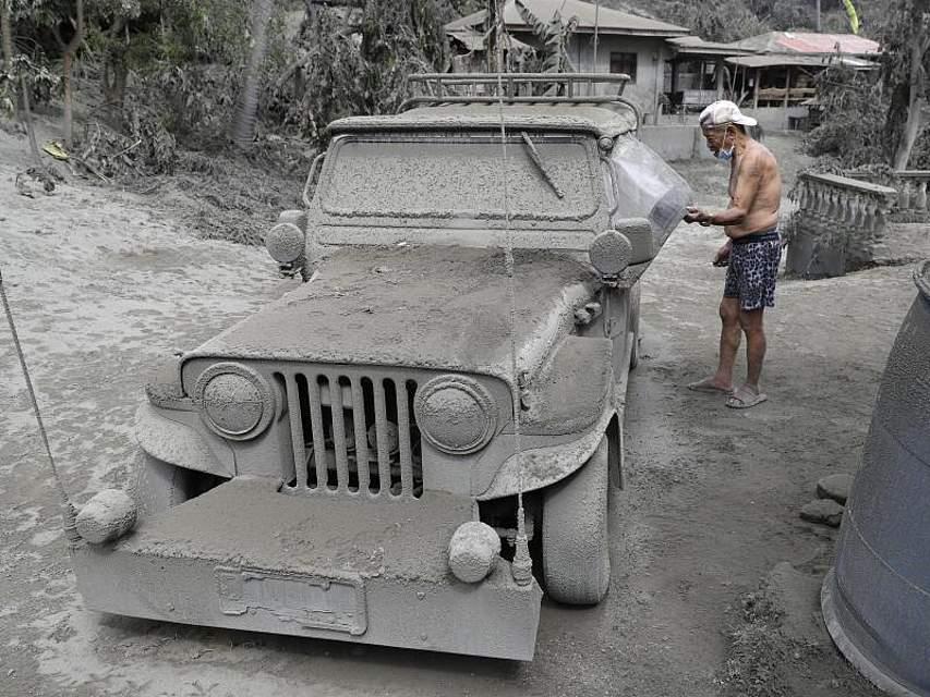 Ein Mann kontrolliert seinen mit Vulkanasche bedeckten Jeep vor seinem Haus in der philippinischen Provinz Batangas. Der gefährliche Vulkan «Taal» treibt aktuell Hunderttausende Menschen in die Flucht. Foto: Aaron Favila/AP/dpa