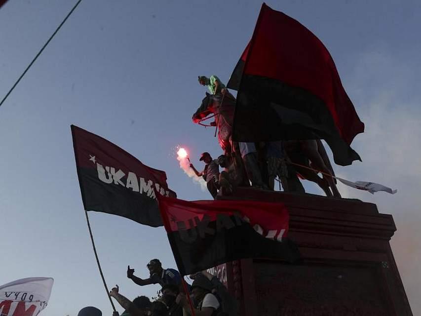 Demonstranten erklimmen das Denkmal von General Manuel Baquedano in Santiago während eines Protestes gegen die Regierung. Foto: Esteban Felix/AP/dpa
