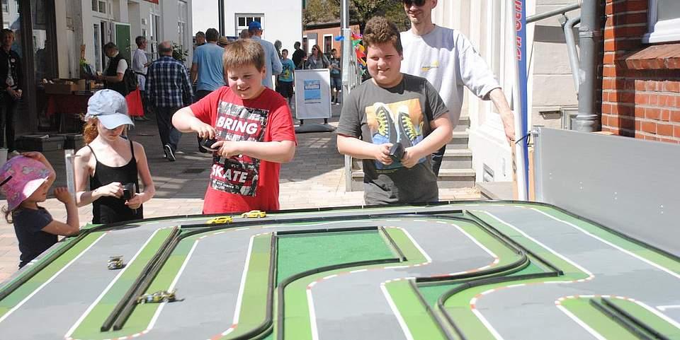 Auf einer Siku-Bahn lieferten sich die Kinder spannende Rennen. Rechts Siku-Modellbahn-Betreiber Gerd Mohr.
