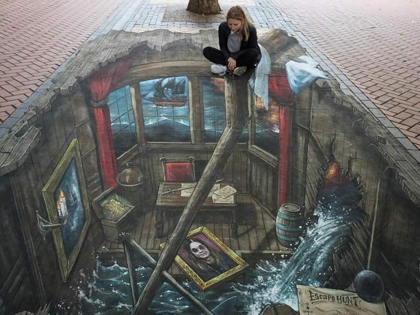 Eine Frau hat sich auf der Upper New Street in Birmingham am Rande eines 3D-Gemäldes niedergelassen. Foto: Aaron Chown/PA Wire
