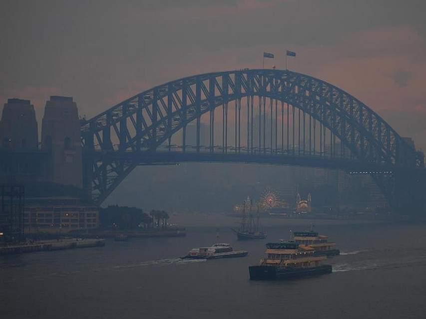 Pendlerfähren fahren an der Sydney Harbour Bridge vorbei. Der Rauch von Buschfeuern in New South Wales hat die Innenstadt bedeckt. Foto: Steven Saphore/AAP/dpa