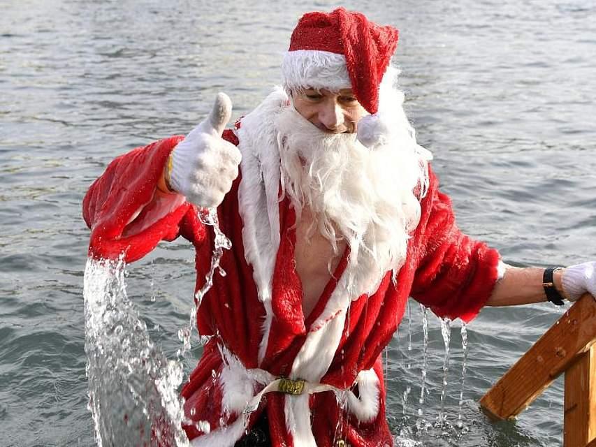 Normalerweise kommt der Weihnachtsmann durch den Kamin. Beim Züricher Samichlaus-Schwimmen entsteigt er dagegen dem Wasser. Teilnehmer verkleiden sich und schwimmen für einen wohltätigen Zweck in der Limmat bei elf Grad Celsius. Foto: Walter Bieri/KEYSTONE/dpa