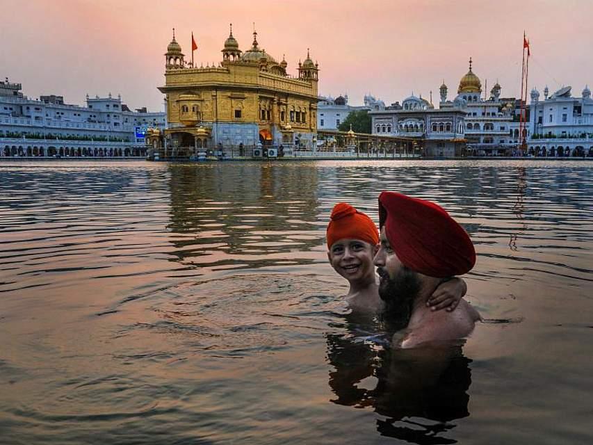 Anhänger des Sikhismus baden in einem Becken, das den Goldenen Tempel im indischen Amritsar umgibt. Foto: Shiva Sharma/PTI