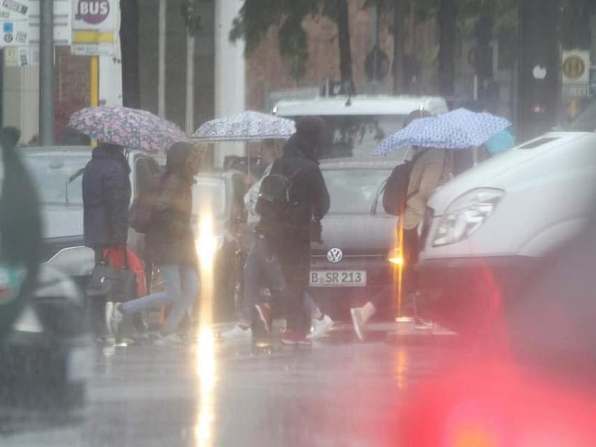 Bloß nicht nass werden: Bei Temperaturen um acht Grad Celsius und Regen überqueren Fußgänger eine Straße in Berlin. Foto: Wolfgang Kumm