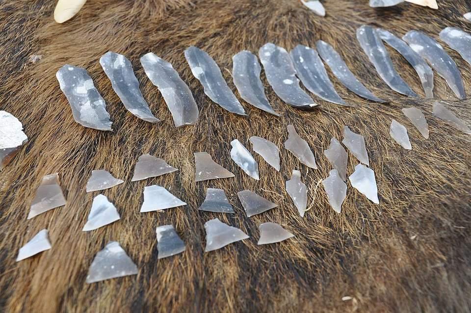 Verschiedene steinzeitliche Klingen, Messer, Pfeile und Werkzeuge.