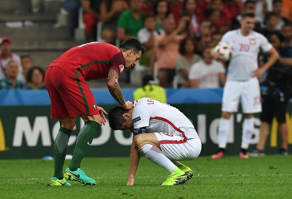 Jose Fonte tröstet Robert Lewandowski nachdem die Polen im Viertelfinale ausgeschieden waren. Foto: Gambarini