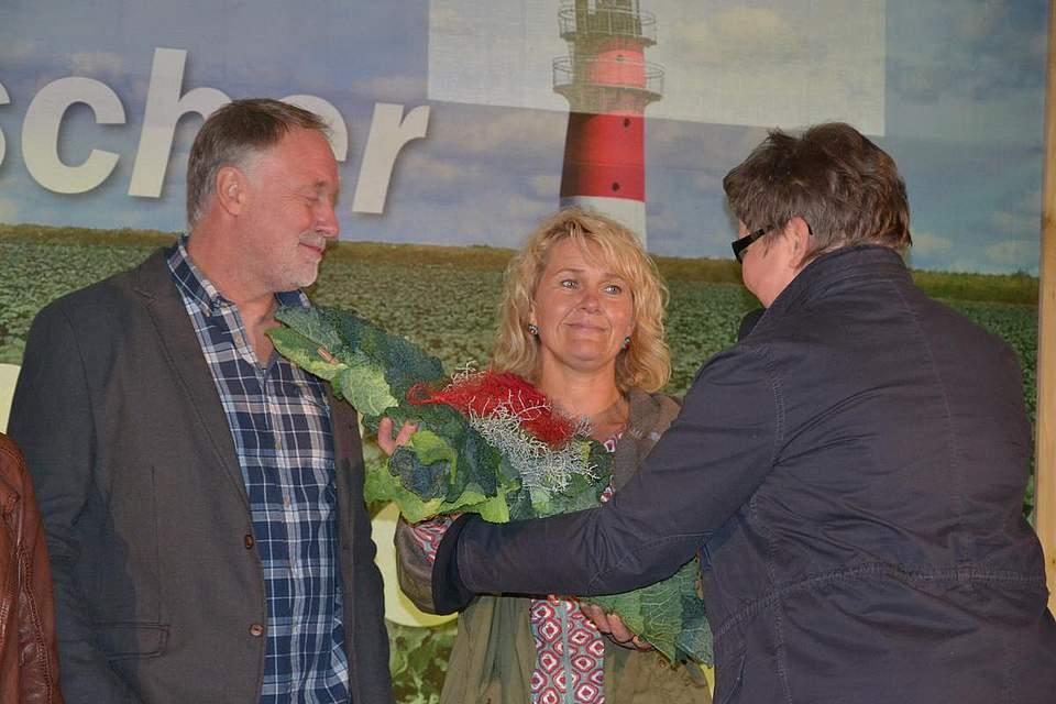 Pastorin Ina Brinkmann überreicht Reimer und Anne Thiel-Peters ein Kreuz aus Kohlblättern.