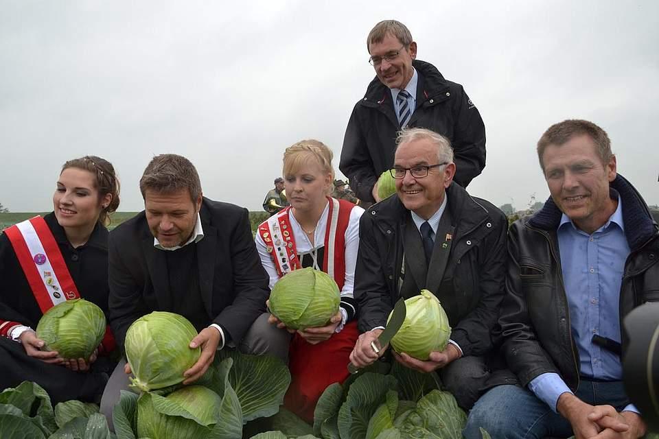 Kohlanschnitt mit Maren I., Minister Habeck, Freia I., Landrat Klimant, Kreispräsident Böttger und Christian Ufen, Vorsitzender des Gemüseanbauerverbands.