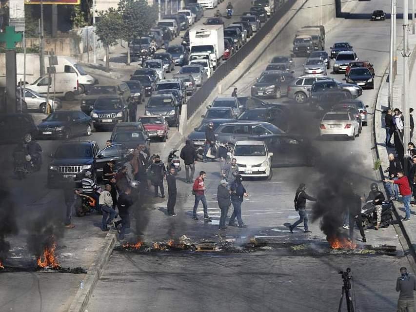 Regierungskritische Demonstranten bauen in Beirut brennende Barrieren auf. Im Libanon protestieren die Menschen seit Wochen gegen Misswirtschaft und Korruption. Foto: Hussein Malla/AP/dpa