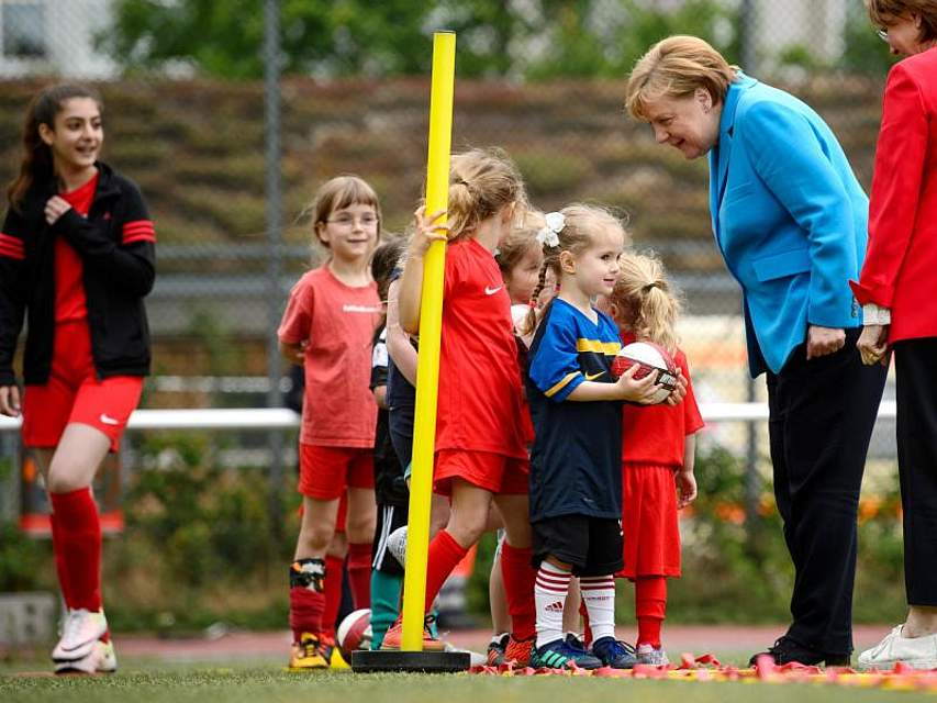 Vor dem Integrationsgipfel in Berlin spricht Kanzlerin Merkel mit jungen Sportlerinnen des SV Rot-Weiß Viktoria Mitte 08. Foto: Sina Schuldt