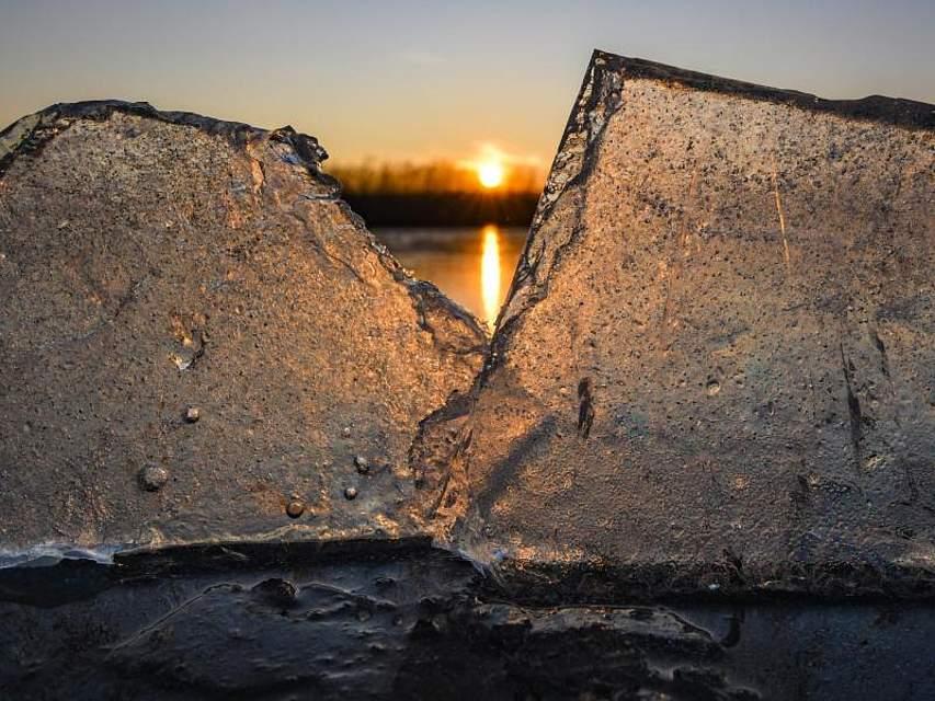 Kleine Eisstücken am Ufer des zugefrorenen Großen Storkower Sees schimmern im Gegenlicht des Sonnenuntergangs. Foto: Patrick Pleul