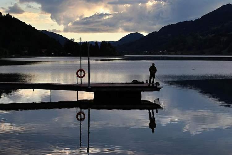 Abendstimmung in Immenstadt. Ein Angler spiegelt sich kurz vor Sonnenuntergang im Wasser des Großen Alpsees. Foto: Karl-Josef Hildenbrand