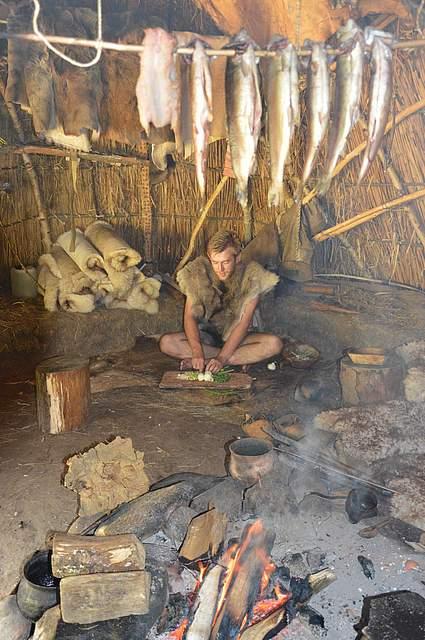 Die von den Steinzeitjägern gefangenenForellen hängen in der Hütte über dem Feuer. Im Hintergrund bereitet Jake Newport einen Salat zu.