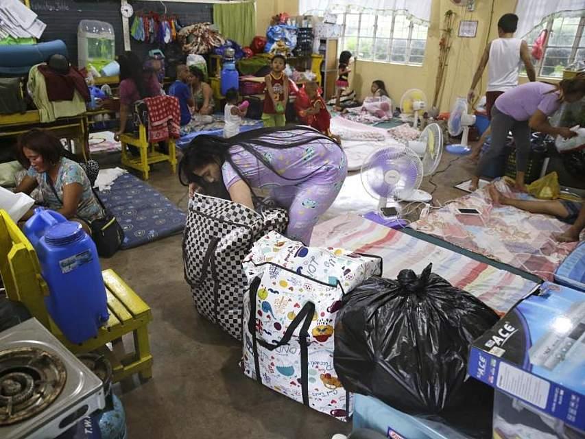 Familien richten sich zum Schutz vor dem Taifun «Mangkhut» in einem Evakuierungszentrum im nordphilippinischen Tuguegarao ein. Die Behörden haben rund 800.000 Menschen aufgefordert, sich vor dem Sturm in Sicherheit zu bringen. Foto: Aaron Favila/AP