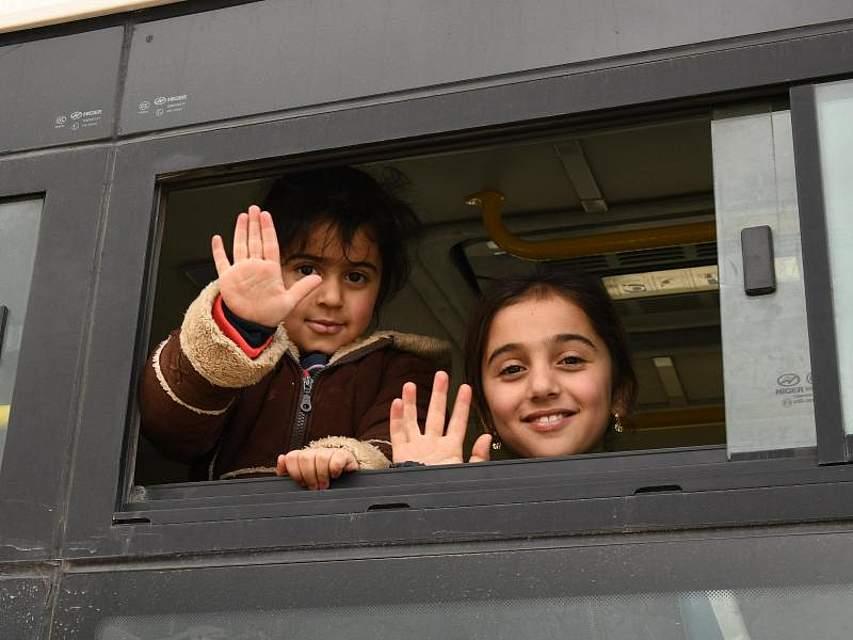 Syrische Flüchtlinge winken am Grenzübergang Jdaidet Yabous während ihrer Heimreise vom Libanon nach Syrien. Foto: Ammar Safarjalani/XinHua/dpa
