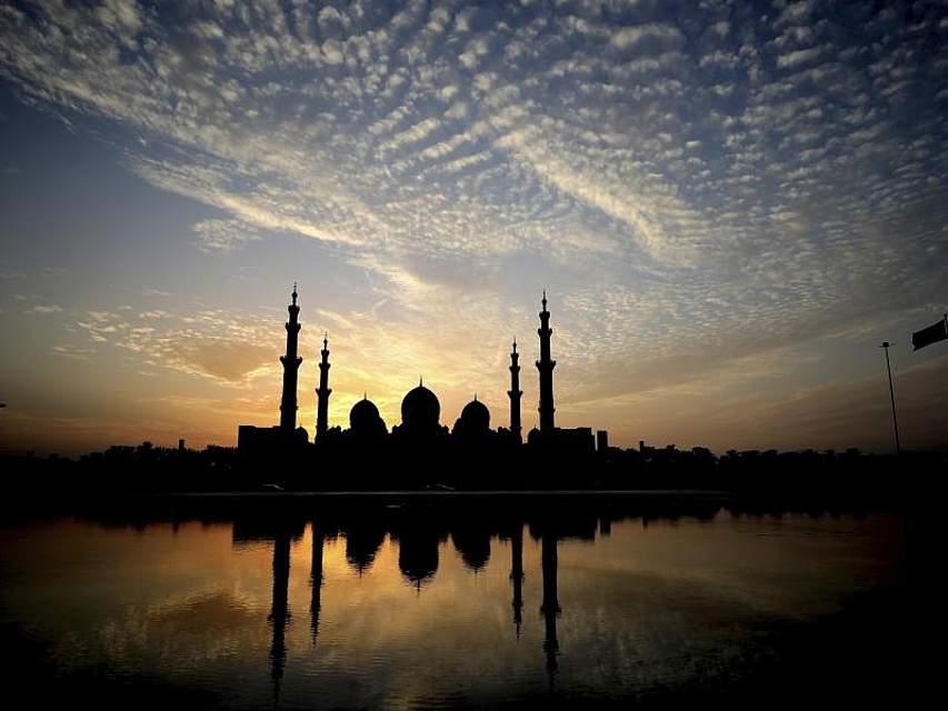 Hinter der Scheich-Zayid-Moschee in Abu Dhabi geht die Sonne unter. Sie ist die drittgrößte Moschee der Welt und bietet 40.000 Gläubigen Platz. Foto: Kamran Jebreili/AP/dpa