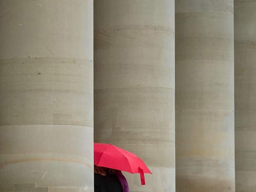 Farbklecks: Eine Frau geht mit ihrem roten Regenschirm durch die Säulen des Königsbaus inStuttgart. Das zeigt sich derzeit von seiner jahreszeitentsprechenden Seite. Foto: Marijan Murat