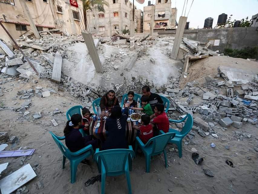 Eine Familie frühstückt neben ihrem zerstörten Haus in der Stadt Rafah im südlichen Gazastreifen. Foto: Xinhua/dpa