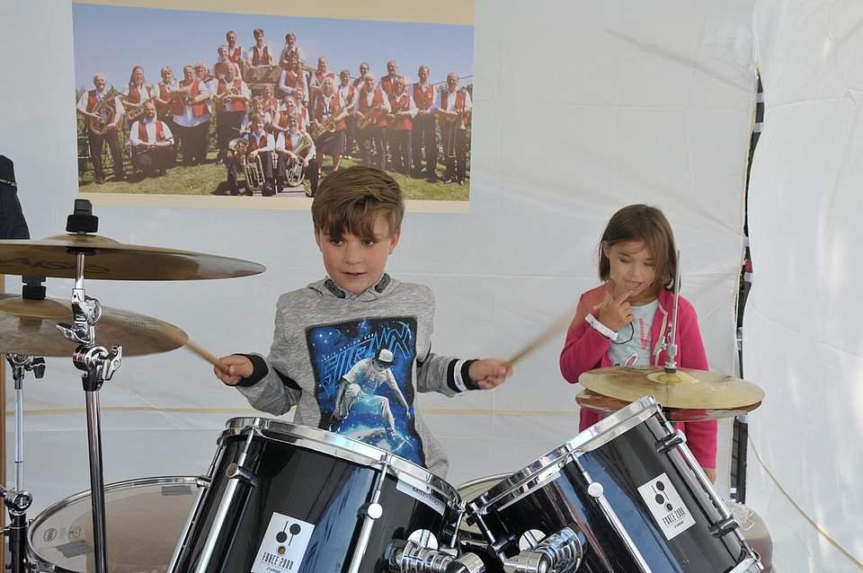 Schlagfertig: Felix Schatz (8) aus Heide trommelt am Stand der Heider Musikfreunde. Seine fünf Jahre alte Schwester Sara hört zu. Foto: Voß