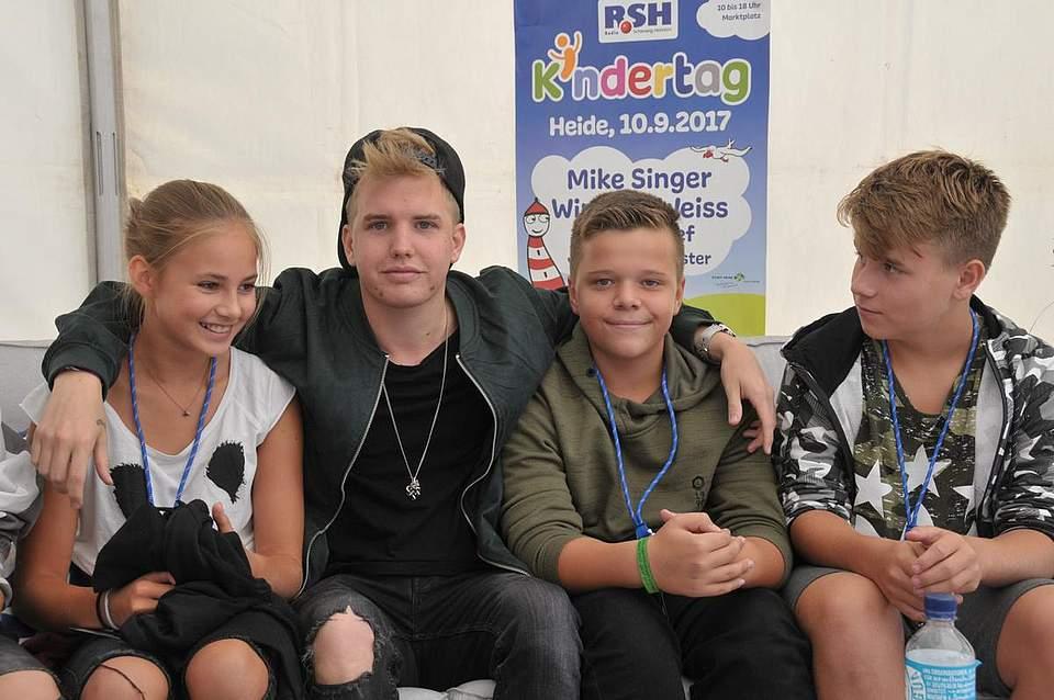 Rapper Kayef mit seinen Fans (von links) Jule Hartmann (12), Colvyn Klingberg (12) und Noah Powlowski (12). Foto: Voß