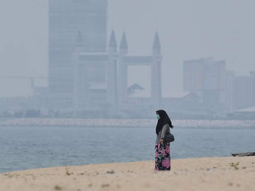 Frische Luft schnappen: Eine Frau schützt sich am Strand vor der Skyline von Kuala Terengganu (Malaysia) mit einer Atemschutzmaske. Foto: Mohd Khairul Fikiri Osman/BERNAMA