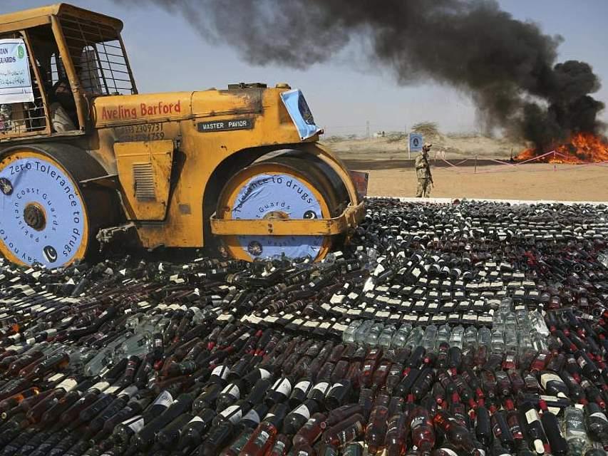 Ein Bulldozer zerstört mit Alkohol gefüllte Flaschen. Im Hintergrund werden Drogen verbrannt. Die pakistanische Anti-Narcotic Force ergreift strenge Maßnahmen, um den Drogenhandel einzudämmen. Foto: Muhammad Rizwan/AP