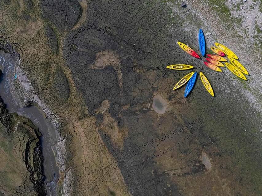 Kajaks liegen auf dem aufgerissenen Boden des ausgetrockneten Flussbetts des Doubs. Die Dürre im Osten Frankreichs hat dazu geführt, dass sich das Wasser des Flusses auf dem niedrigsten Stand seit mehr als einem Jahrhundert befindet. Foto: Sebastien Bozon/AFP/dpa