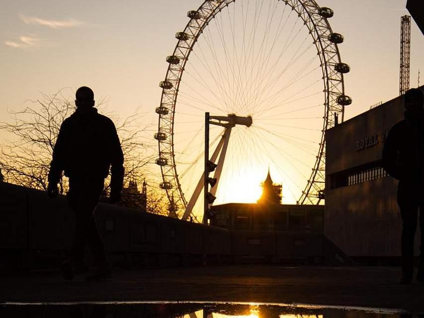 Die Sonne geht im Riesenrad London Eye unter und spiegelt sich dabei in einer Pfütze. Foto: Aaron Chown/PA Wire/dpa