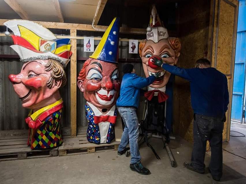 Die Wagenbauer Steffen (l) und Geo Weitmann stellen Schwellkopp «Rickes» an seinen Platz. Die «Meenzer Schwellköpp» des Mainzer Carneval-Vereins (MCV) sind ein Symbol der Straßenfassenacht. Foto: Andreas Arnold