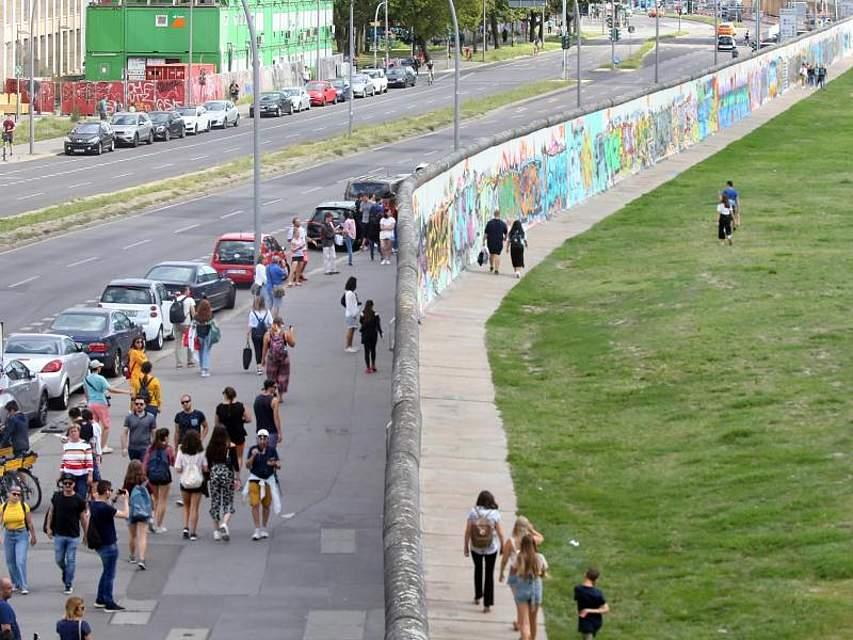 Menschen gehen und stehen auf beiden Seiten des längsten noch erhaltenen Teilstücks der Berliner Mauer, der sogenannten East Side Gallery. Vor genau 58 Jahren begann der Bau der Mauer. Foto: Wolfgang Kumm