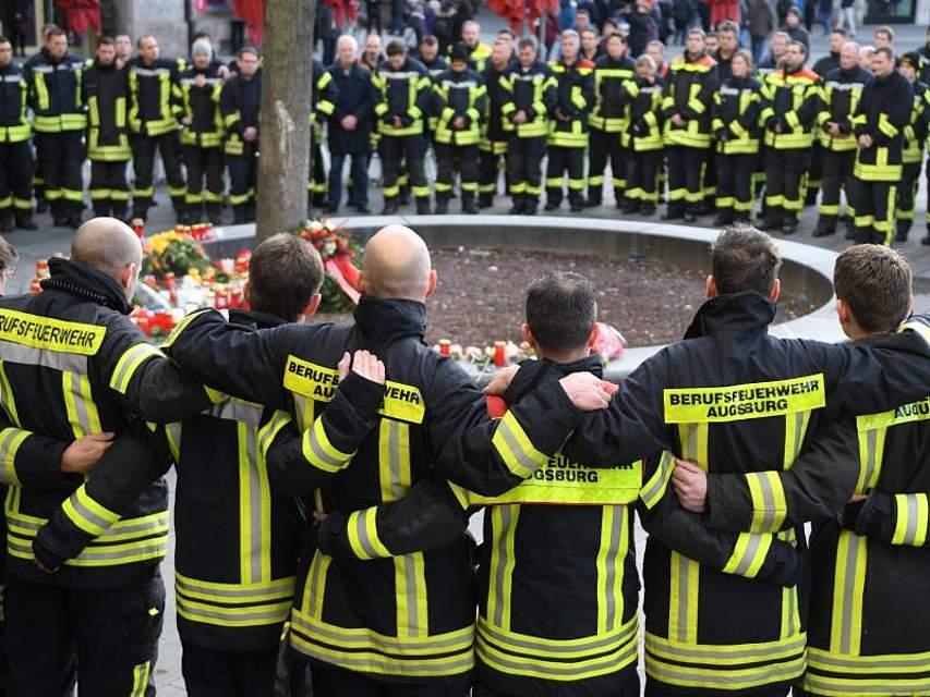 Nach der tödlichen Attacke in Augsburg auf einen 49-jährigen Feuerwehrmann, der als Passant in der Innenstadt unterwegs war, trauern Kameraden. Der Mann wurde von einem 17-Jährigen tödlich verletzt. Foto: Stefan Puchner/dpa