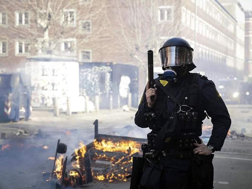 Hütet das Feuer: Ein dänischer Polizist steht nach Krawallen in Kopenhagen Wache. Bei einer Demonstration eines islamfeindlichen Politikers gab es 23 Festnahmen. Foto: Philip Davali/Ritzau Scanpix