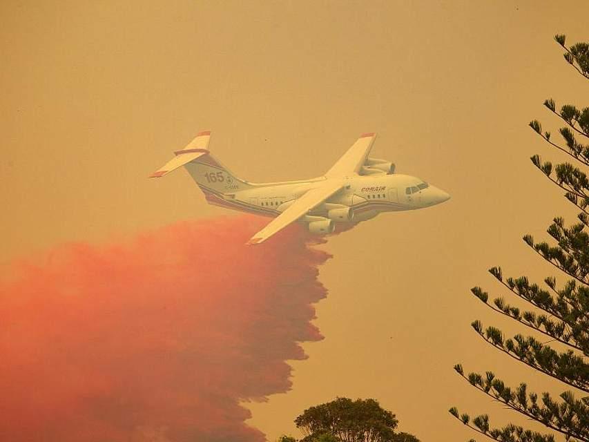 Ein Löschflugzeug wirft Feuerschutzmittel auf ein Buschfeuer nahe Harrington nördlich von Sydney. Die heißen, windigen Wetterbedingungen fachen die Brände im australischen Bundesstaat New South Wales immer weiter an. Foto: Shane Chalker/AAP/dpa