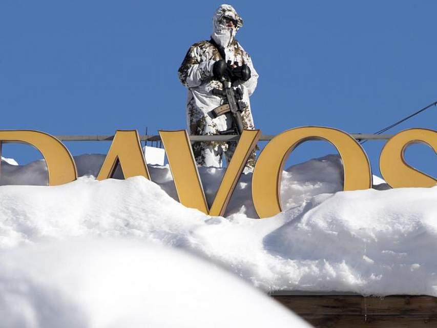 Ein Mitglied der Schweizer Spezialkräfte steht auf dem Dach des Kongress Hotels in Davos unweit des Kongresszentrums, wo sich die Mächtigen und Einflussreichen der Erde beim Weltwirtschaftsforum versammeln. Foto: Laurent Gillieron/Keystone