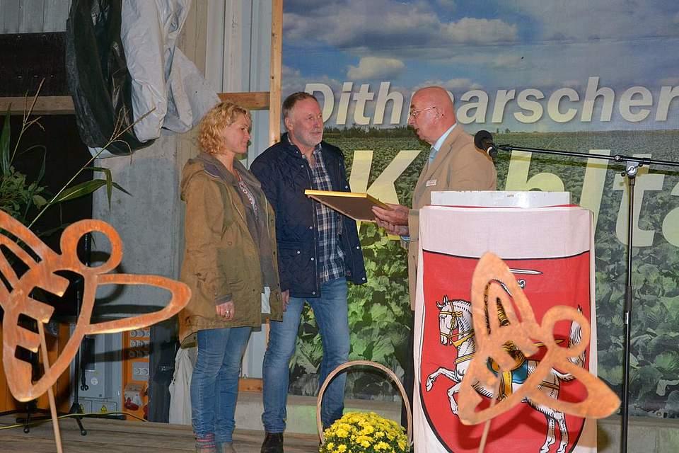 Christian Pögel, Amtsvorsteher des Amtes Mitteldithmarschen überreicht Anne und Reimer Thiel-Peters eine Dankesurkunde.