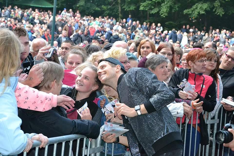 Geduldig schreibt Axel Fischer Autogrammkarten und lässt sich mit seinen Fans fotografieren.