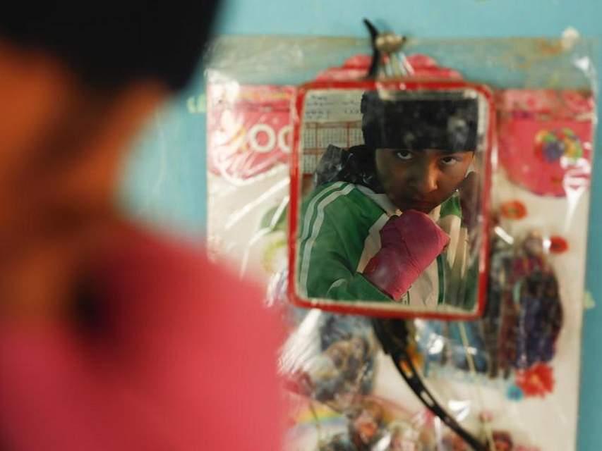 Die 12-jährige bolivianische Boxerin Grecce Kelly Flores, die den Spitznamen «Steinhände» trägt, schaut nach ihrem morgendlichen Training in den Spiegel. Sie träumt davon, die Weltmeisterschaft im Frauenboxen zu erreichen. Foto: Juan Karita/AP/dpa