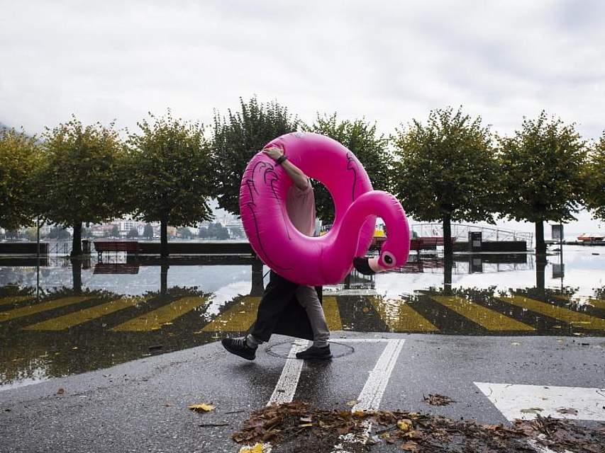 Hochwasser am Lago Maggiore: Ein Kellner trägt einen aufblasbaren Flamingo an der überfluteten Seepromenade. Foto: Alessandro Crinari/KEYSTONE/TI-PRESS