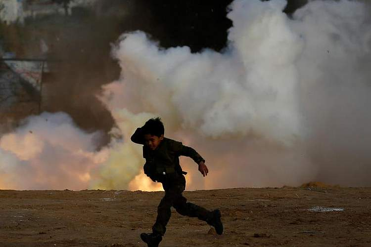 Ist zwar nur Training, sieht aber gefährlich aus und ist es sicherlich auch: Dieser Junge rennt während einer Übung der palästinensischen Mudschaheddin-Brigaden über einen Platz in Gaza-Stadt. Foto: Hatem Moussa/AP