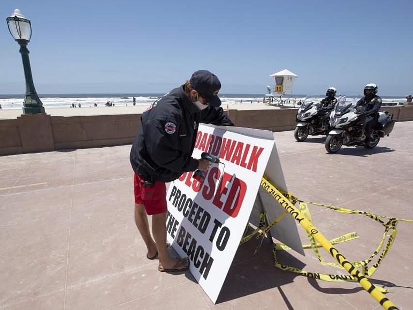 Ein Rettungsschwimmer stellt ein Schild auf, auf dem darauf hingewiesen wird, dass die Strandpromenade im kalifornischen San Diego geschlossen ist. Foto: Gregory Bull/AP/dpa