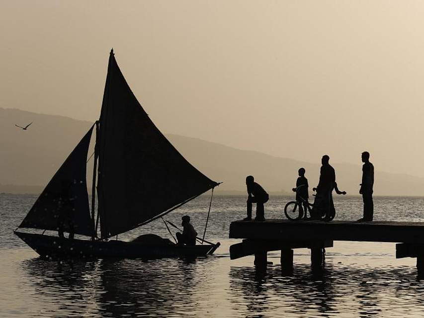 Ein Fischer segelt in Port-Au-Prince an einem Steg vorbei, auf dem Jungen fischen. - Seit Wochen herrscht in Haiti eine politische Krise. Demonstranten fordern den Rücktritt von Präsident Jovenel Moïse. Foto: Rebecca Blackwell/AP/dpa