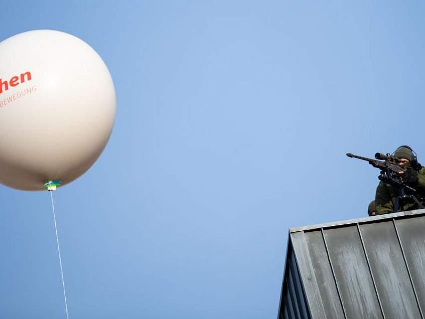 Ein Präzisionsschütze der Polizei sichert von einem Dach aus den Aachener Rathausplatz, während vor ihm der Ballon eines Demonstranten fliegt. Foto: Marius Becker