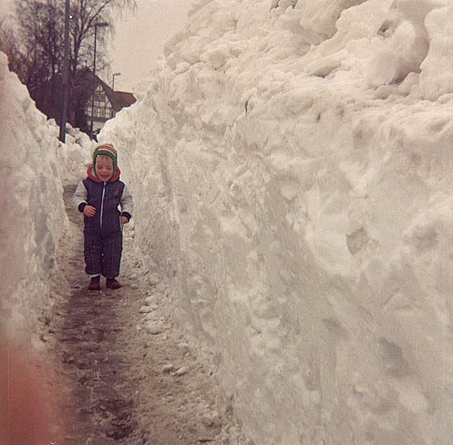 """""""Die meterhohen Schneeberge verhinderten den Autoverkehr; es war herrlich ruhig"""", erinnert sich Inge Köhm aus Wesselburen. Ihr Foto zeigt ein zweijähriges Mädchen zwischen Schneewänden auf einem schmalen Gehweg."""