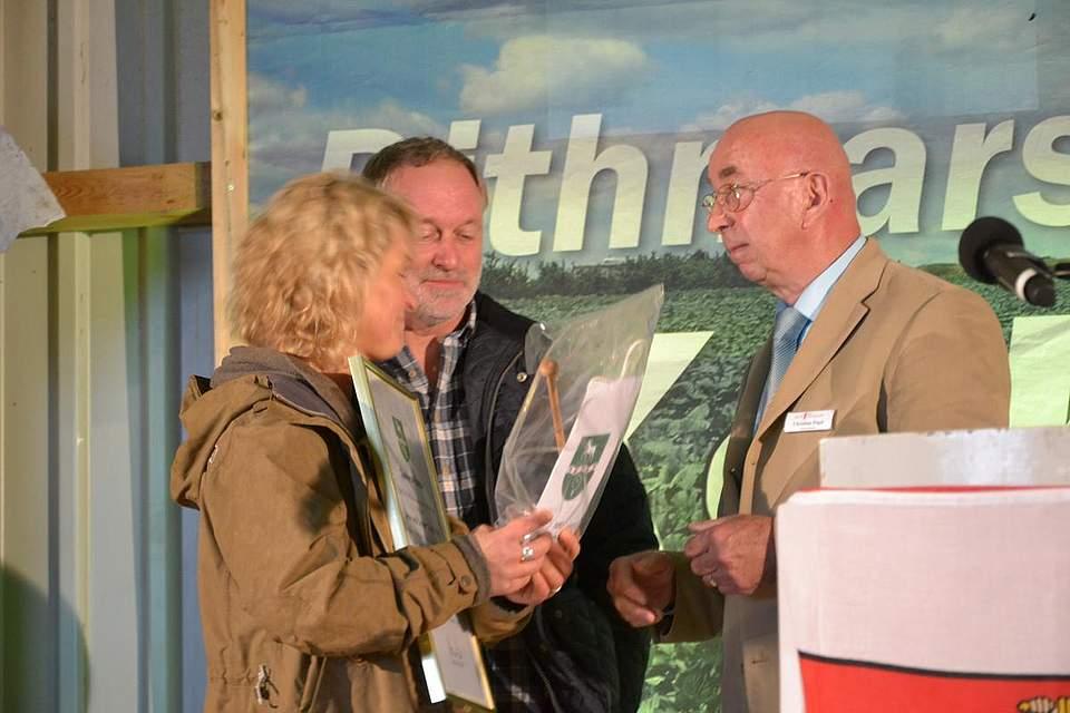 Amtsvorsteher Christian Pögel überreicht Anne und Reimer Thiel-Peters eine Dankesurkunde.