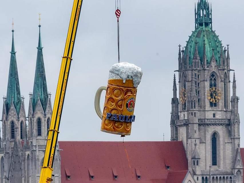 In München hievt ein Kran einen überdimensionalen Bierkrug über die Theresienwiese. Hier steigt ab dem 21. September das Oktoberfest. Foto: Peter Kneffel