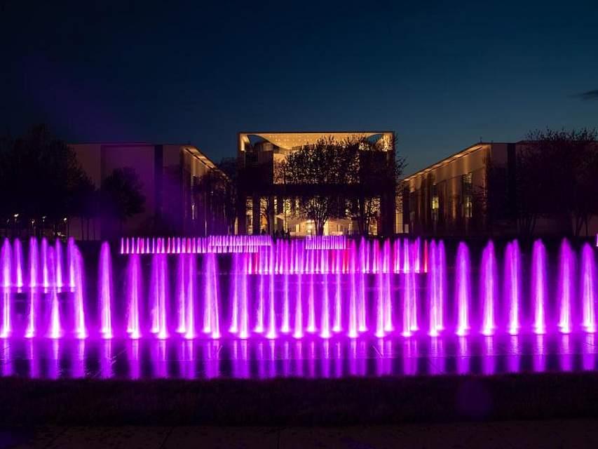 Die Fontänen der Brunnen vor dem Bundeskanzleramt in Berlin sind am Abend bunt beleuchtet. Foto: Paul Zinken/dpa-Zentralbild/dpa