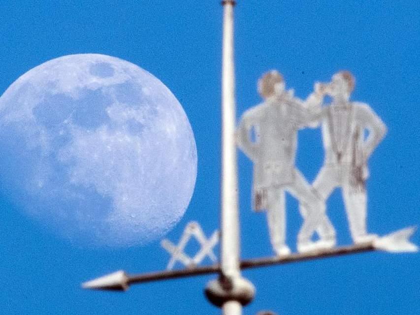 Der Mond steht hinter einer Wetterfahne in Köln. Foto: Federico Gambarini